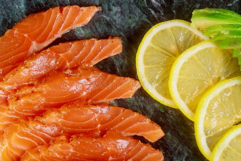 Läckra och sunda hemlagade laxskivor av avokadot och skivor av citronbrädet som är klara att äta arkivfoton