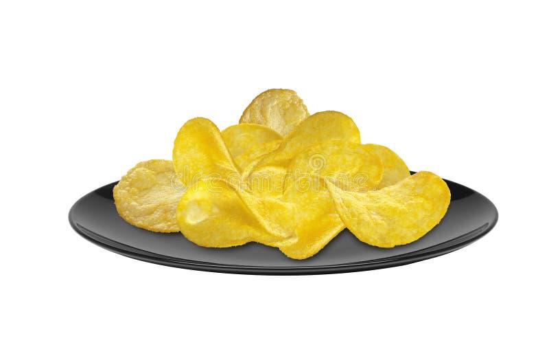 Läckra potatischiper på den svarta plattan som isoleras på vit royaltyfria bilder
