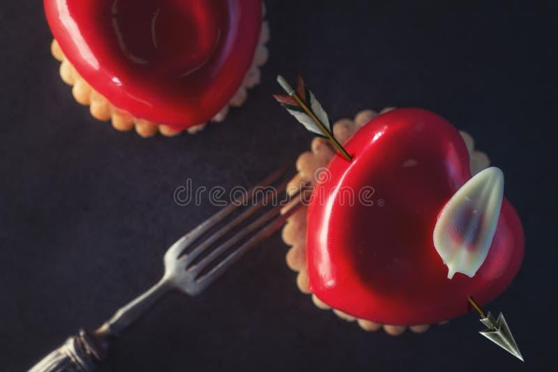 Läckra röda valentin bakar ihop med hjärtaform på svart bakgrund, hjärtakaka med pilen royaltyfri fotografi