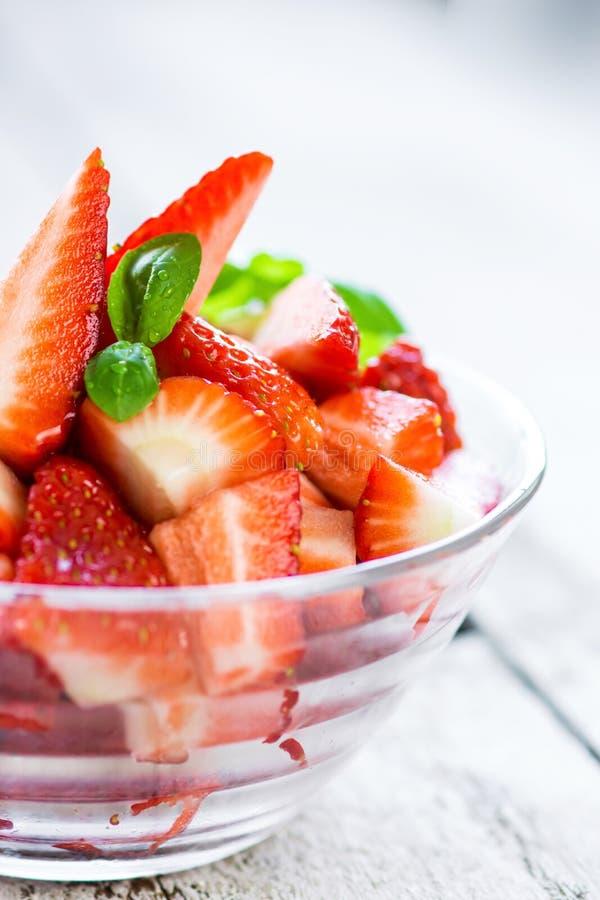 Läckra skivor av organiska jordgubbar i en kopp arkivbild
