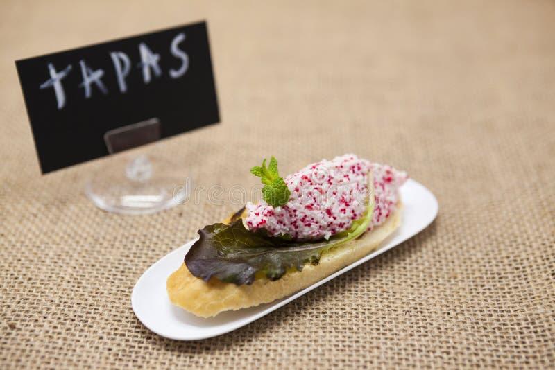 Läckra spanska tapas för TAPASaffisch med krabban som är tartare med fiskromen och sallad för flygfisk på en skiva av bagetten En arkivbild