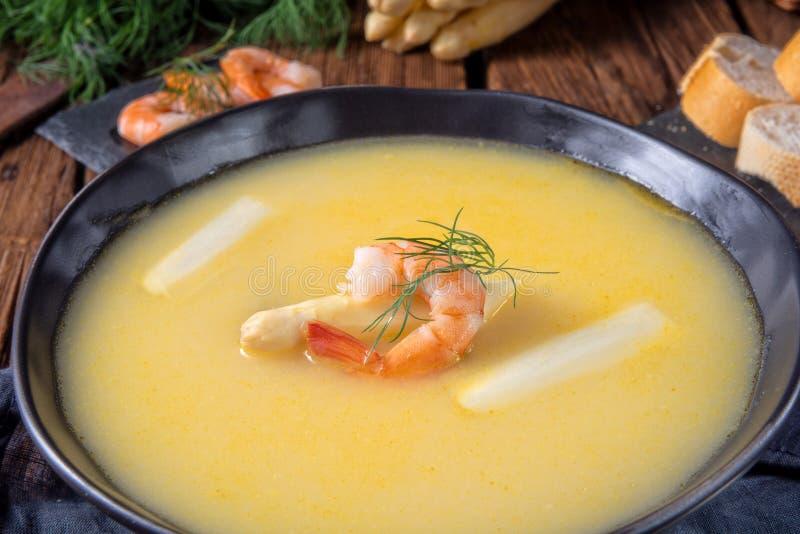 Läckra sparriers lagar mat med grädde soppa med räkor och ny dill royaltyfria foton