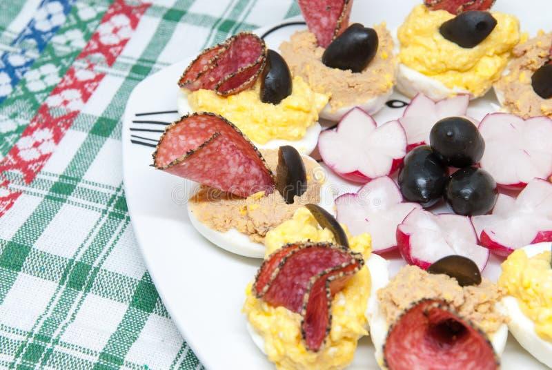 Läckra välfyllda kokta halva ägg med olik fyllningäggula som är blandad med ost- eller leverpate och dekorerat med salami och bla royaltyfri bild
