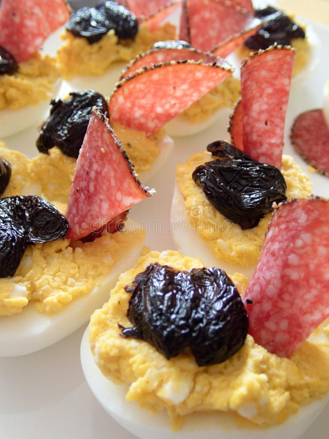 Läckra välfyllda kokta halva ägg med olik fyllningäggula som är blandad med ost- eller leverpate och dekorerat med salami och bla arkivfoto