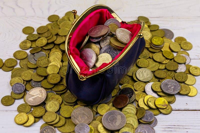 Läderändringshandväska med mynt på vit träbakgrund royaltyfri fotografi