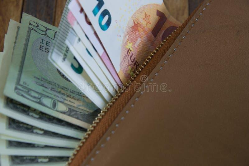 Läder är en öppen plånbok med sedlar i euro och dollar arkivbilder