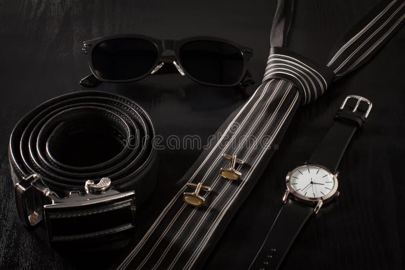 Läder solglasögon, band, manschettknappar, klocka på en svart backgroun royaltyfria bilder