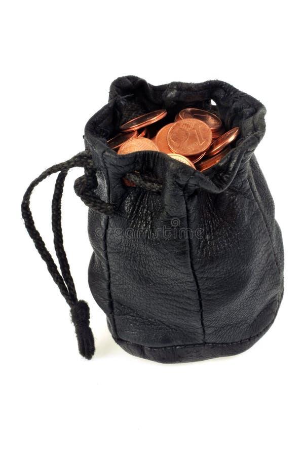 Läderhandväska som fylls med mynt på en vit bakgrund arkivbilder