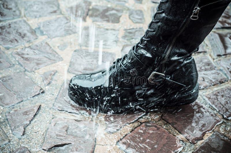 Läderkänga i regnet på kullersten fotografering för bildbyråer