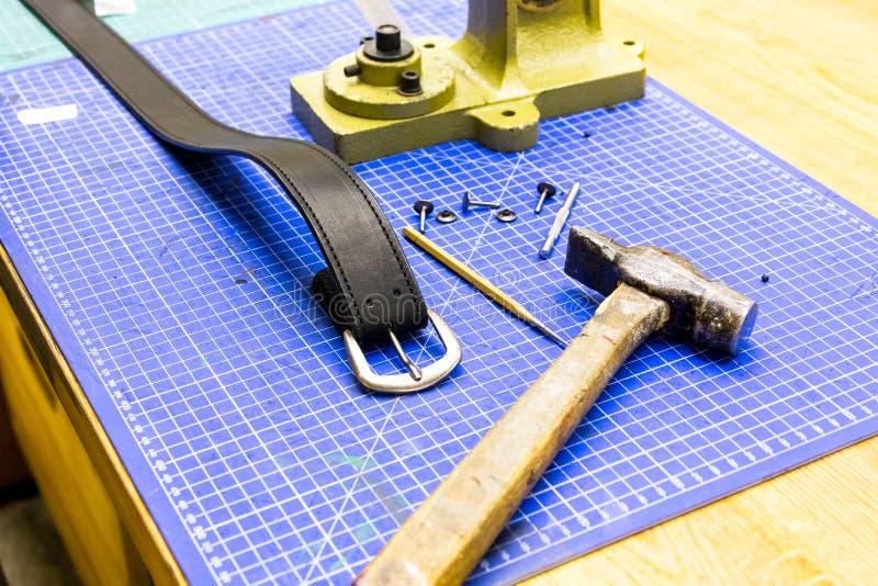 Läderseminariumbälte framme av fattanden på tabellen arkivbilder