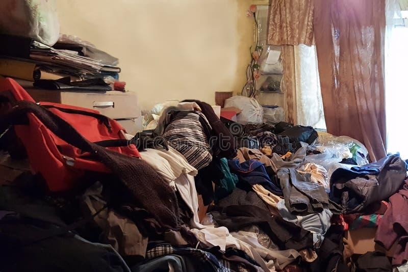 Lägenhet av en pensionär som lider från tvångsmässigt hamstra, skräpat ner med avfall och böcker royaltyfria foton