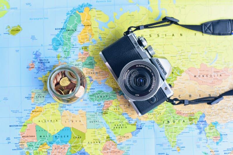 Lägenhet som är lekmanna- av den Mirrorless kameran och exponeringsglaskruset som fylls med bronsmynt som isoleras på världskarta royaltyfri foto