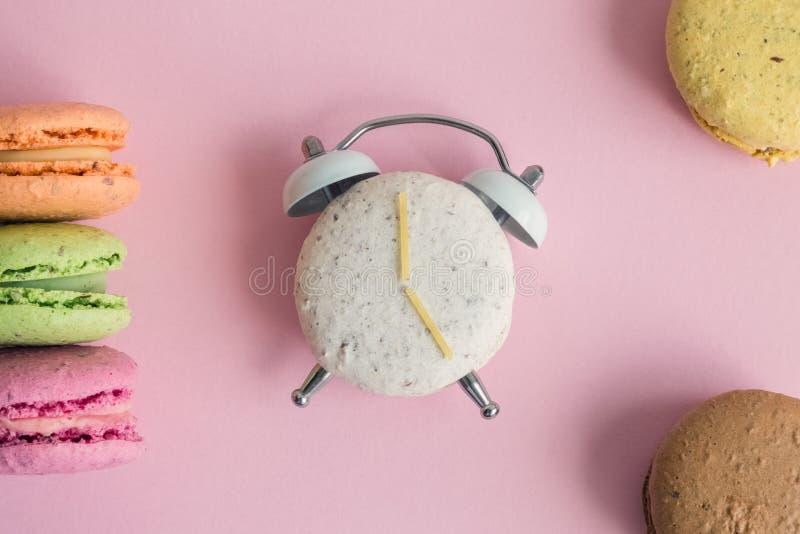 Lägenhet som är lekmanna- av färgrika macarons på bakgrund för pastellfärgade rosa färger Ett av dem i form av ringklockan med kl royaltyfria bilder