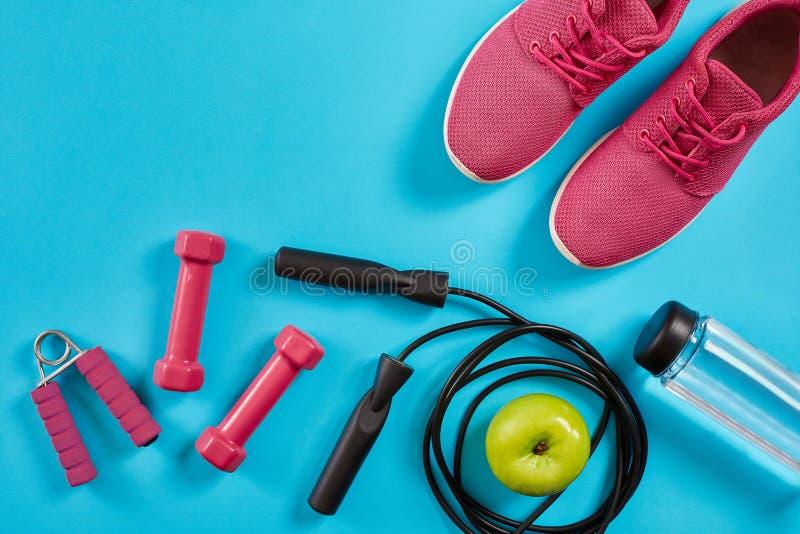 Lägenhet som är lekmanna- av kvinnliga sportutrustningar, hopprep, flaskan av vatten och rosa färggymnastikskor på blå bakgrund arkivfoto