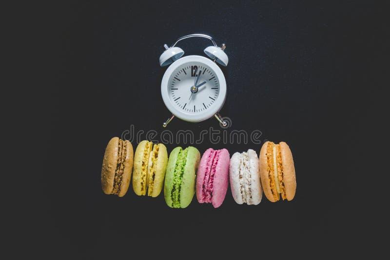 Lägenhet som är lekmanna- av macarons i olika färger med den vita ringklockamodellen Utrymme för kopierar royaltyfri foto