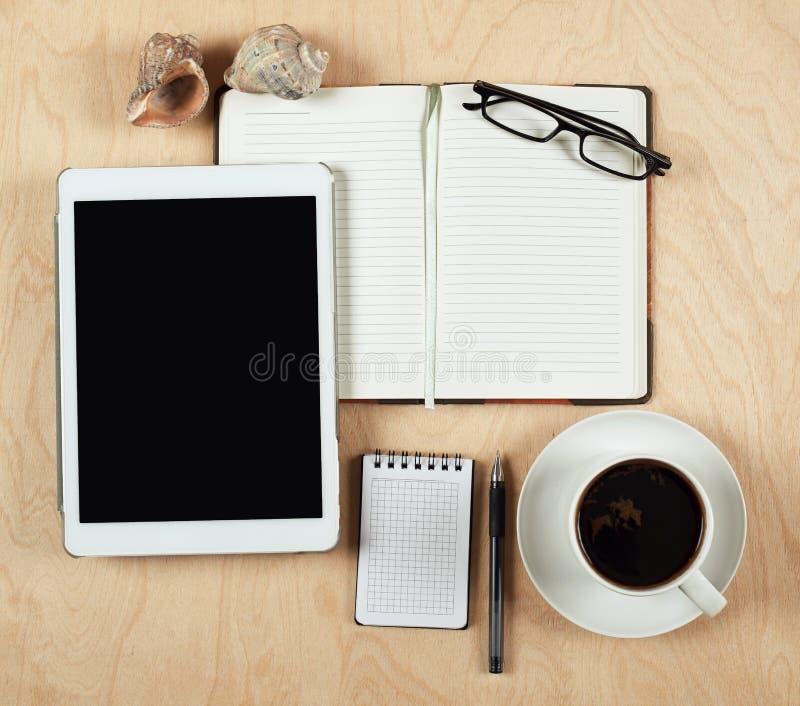 Lägenhet som är lekmanna- av minnestavladatoren, anteckningsboken, kaffekoppen och blyertspennan med den tomma mitten på wood bak royaltyfri foto