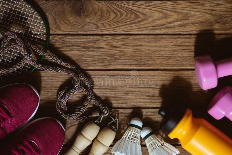 Lägenhet som är lekmanna- av röda sportskor, hantlar, badminton, flaska av wat fotografering för bildbyråer