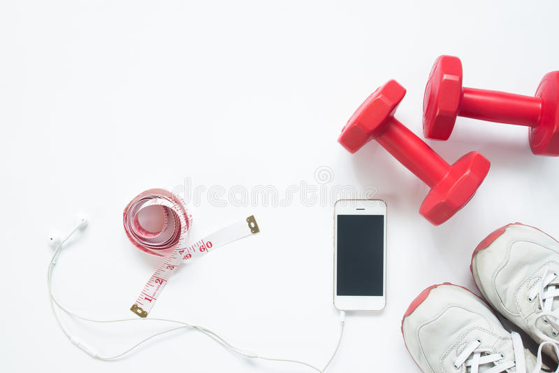 Lägenhet som är lekmanna- av smartphonen med att mäta bandet, röda hantlar arkivbild