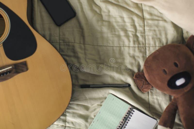 Lägenhet som är lekmanna- av smartphonen, notepaden, penna och gitarren arkivfoton