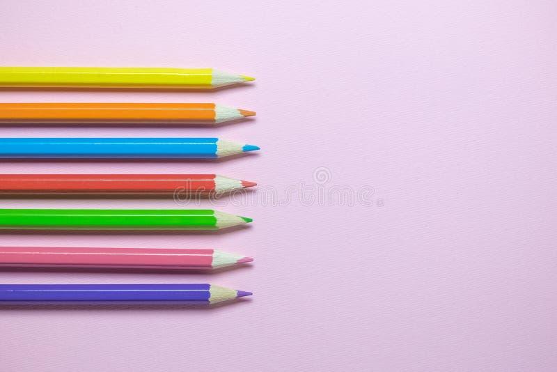 Lägenhet som är lekmanna- av träfärgpennor i olika färger på vanlig rosa bakgrund royaltyfria foton