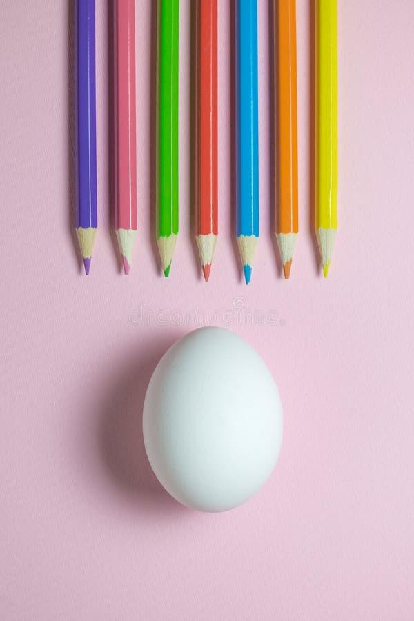 Lägenhet som är lekmanna- av träfärgpennor i olikt vit ägg för färger och på vanlig rosa bakgrund arkivfoton
