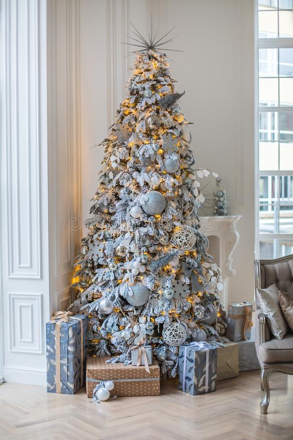 Lägenheten dekoreras med en julgran, under trädet är gåvor royaltyfri foto