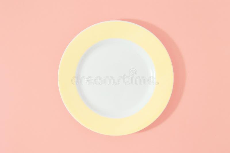 Lägenheten för den bästa sikten för bakgrund för den tomma gula plattan bantar den lekmanna- rosa minimi royaltyfria foton