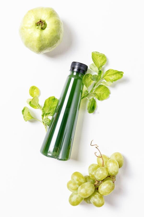 Lägenheten för den bästa sikten lägger flaskan av fruktsaft med spenat, grön greape och guavan på vit bakgrund Den sunda livsstil arkivbild