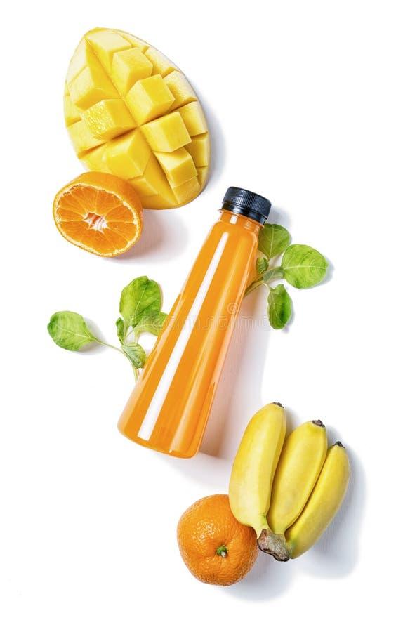 Lägenheten för den bästa sikten lägger flaskan av fruktsaft med spenat, mango, apelsinen och bananen på vit bakgrund Sund livssti royaltyfri foto