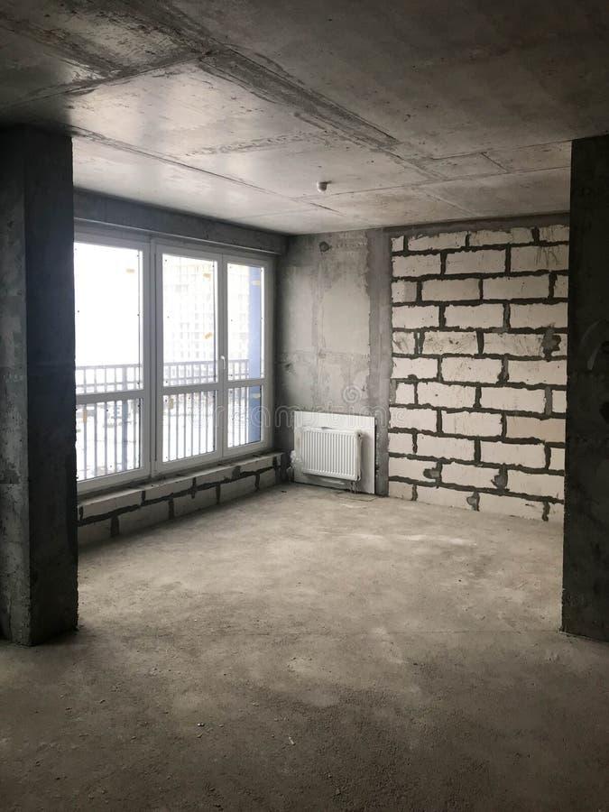 Lägenheten i nybygget med en fri orientering utan reparation och garnering med kala väggar ett stort panorama- franskt fönster royaltyfri fotografi