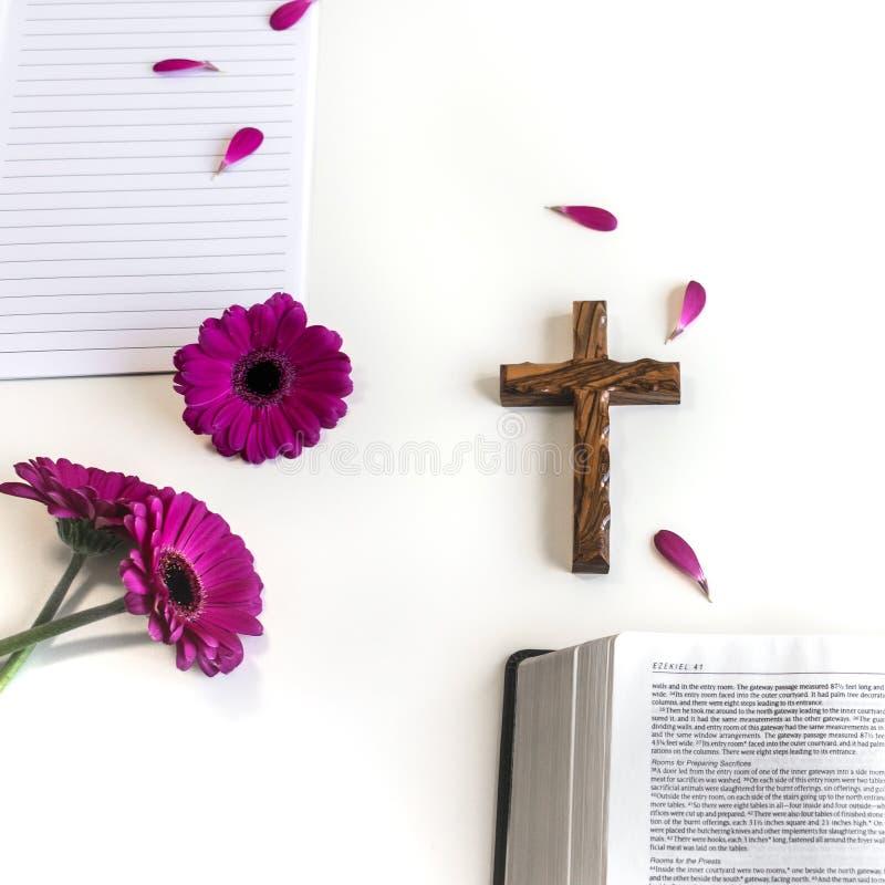 Lägenheten lägger: öppen bibel, träkors, öppen tidskrift på vit bakgrund och rosa, purpurfärgat, violette, röd Gerberablomma med  arkivfoton