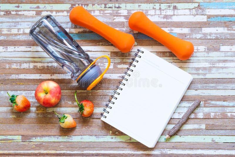 Lägenheten lägger av äpplet, jordgubben, hantlar, anteckningsboken för tomt utrymme och flaskan av vatten på rostig vit bakgrund  royaltyfri fotografi