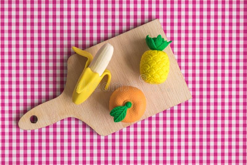 Lägenheten lägger av apelsinen, ananas och bananen på skärbrädaabstrakt begrepp mot röd klassisk rutig bordduktextur royaltyfri foto