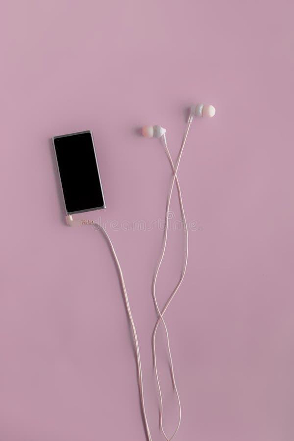 lägenheten lägger av apparaten för spelaren för modern musik och hörlurar, minimalistic begrepp på färgyttersidor arkivbild