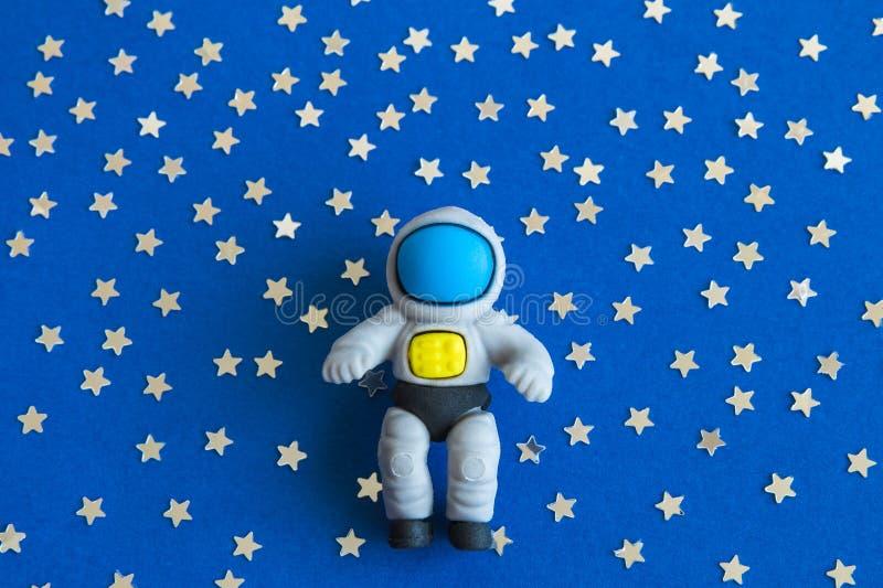 Lägenheten lägger av astronautleksaken mot mörk bakgrund med stjärnaabstrakt begrepp royaltyfri bild