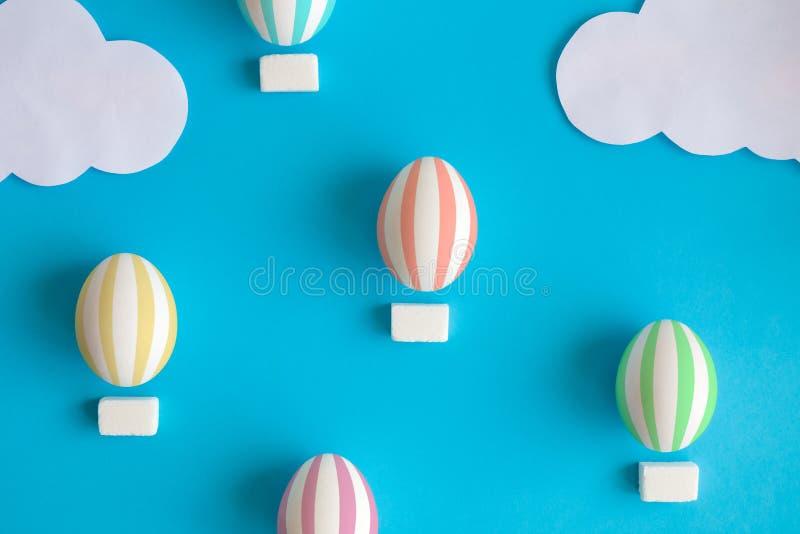Lägenheten lägger av färgrika easter ägg i form av luftballonger som är abstrakta på blå bakgrund royaltyfri fotografi