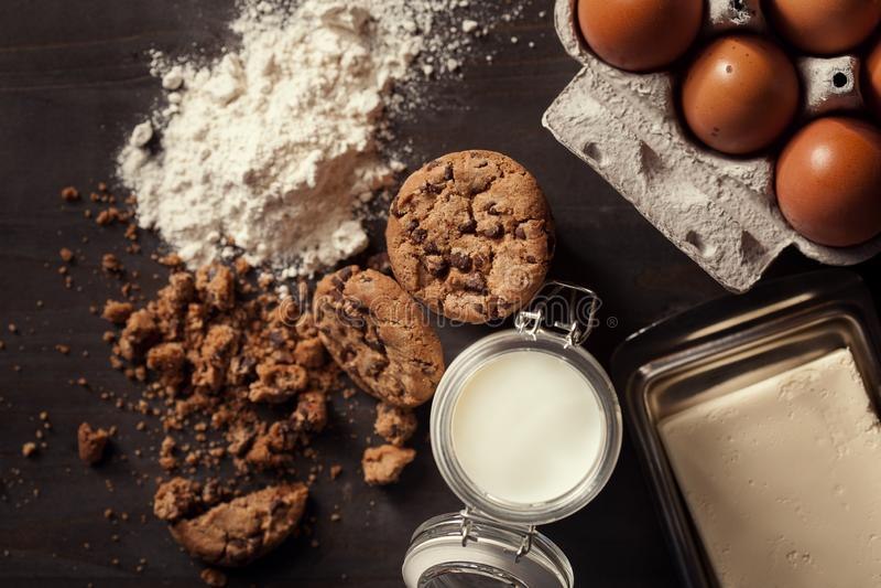 Lägenheten lägger av hemlagade choklade kakor med flaskan av mjölkar, vitt mjöl, nya ägg, smör och smulor på lantligt royaltyfri fotografi