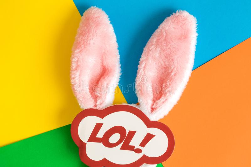 Lägenheten lägger av kaninöron och lolklistermärke på mångfärgat bakgrundsferieabstrakt begrepp royaltyfri foto
