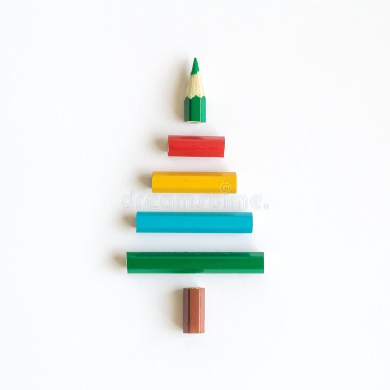 Lägenheten lägger av mångfärgade blyertspennor i form av julgranabstrakt begrepp på ljus bakgrund royaltyfria bilder