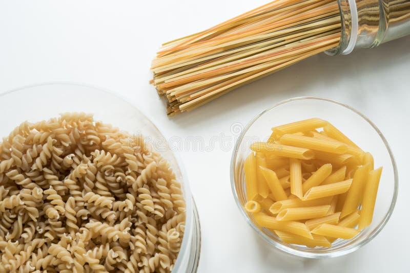 Lägenheten lägger av spagetti i en krus, en fussili och en penne arkivbilder