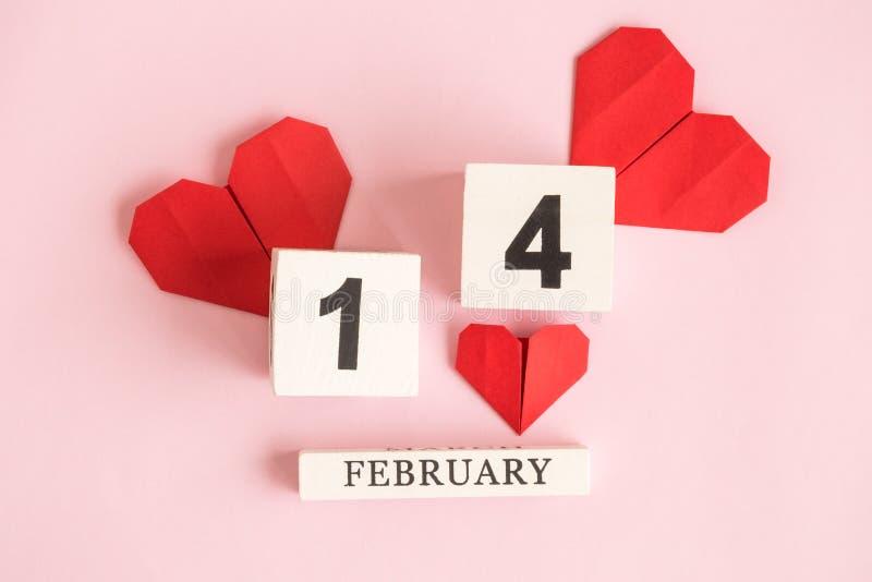 Lägenheten lägger av träkalender- och origamipappershjärtor mot pastellfärgat rosa för valentindag för bakgrund minsta begrepp arkivbilder