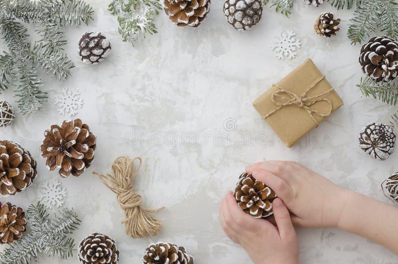 Lägenheten lägger barns händer rymmer kotten, den handgjorda gåvaasken för hantverk, repet, granfilialer och snöflingor på vit ba arkivbild