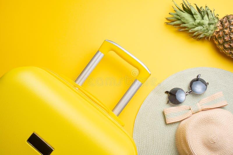 Lägenheten lägger en gul resväska med tillbehör och ananas för att koppla av på en gul bakgrund begreppet av loppet, vilar och arkivbilder