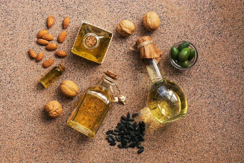 Lägenheten lägger en uppsättning av olik olja i flaskor, mandel, valnöt, solros och olivgrön brun bakgrund ovanf?r sikt royaltyfria bilder