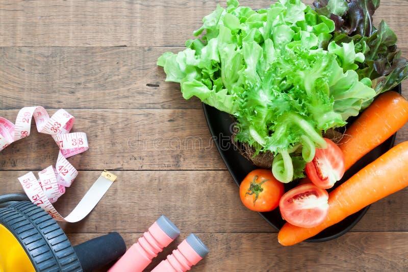 Lägenheten lägger, hälso- och konditionbegreppet Grönsaker och konditionutrustningar på trä royaltyfria bilder