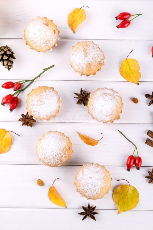 Lägenheten lägger i höststil Läckra muffin med kanelbruna pinnar, anisstjärnor, bär av nyponet och höstsidor arkivfoto