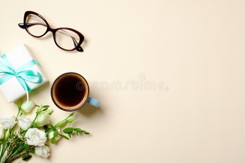 Lägenheten lägger kvinnainrikesdepartementetskrivbordet med kaffekoppen, gåvaasken, exponeringsglas, rosblommabuketten, bandet oc royaltyfria bilder