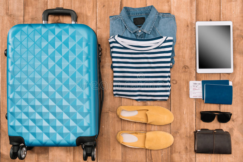 Lägenheten lägger med bagage, mankläder, tillbehör och den digitala minnestavlan på trägolv arkivbild