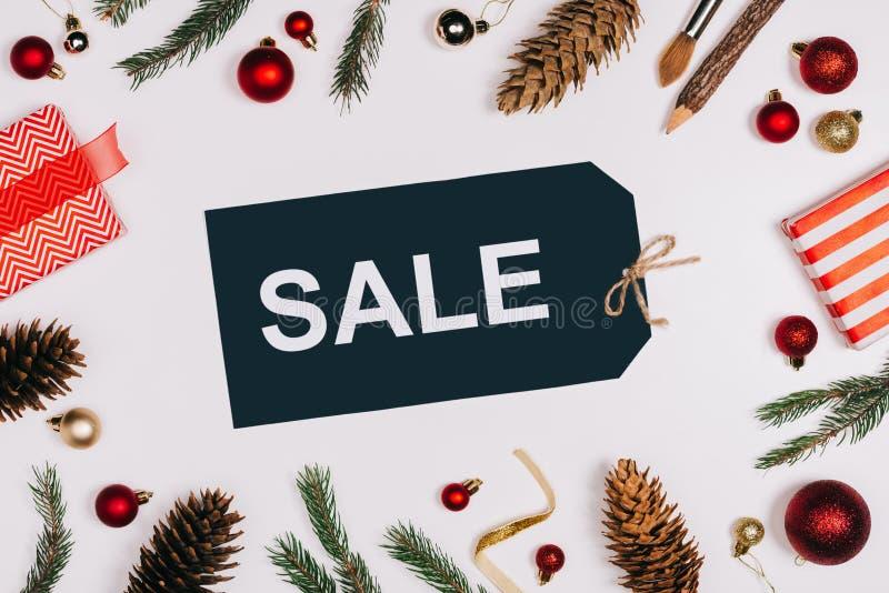 lägenheten lägger med den ordnade prislappen med försäljningsbokstäver, sörjer kottar, slågna in gåvor och julleksaker som isoler royaltyfri foto