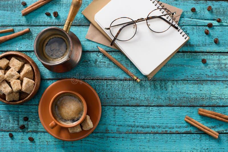 lägenheten lägger med koppen kaffe, glasögon, bunke med farin, den tomma anteckningsboken, grillade kaffebönor, och kanelbrunt kl royaltyfri foto